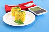 Dhokla, an Indian vegetarian food native to Gujarat state, India, with tamarind and green chutney as side dishes. poster