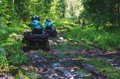 Summer Activities for adults - a trip on quad bikes on the road. Man on ATV in the mud on the road to take part in the race over rough terrain in the forest on a hot summer day. poster