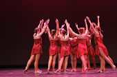 Modern Dance group in Red costumes on stage poster