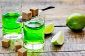 absinthe shots with fresh green lime slices and sugar cubes on wooden bar table background poster
