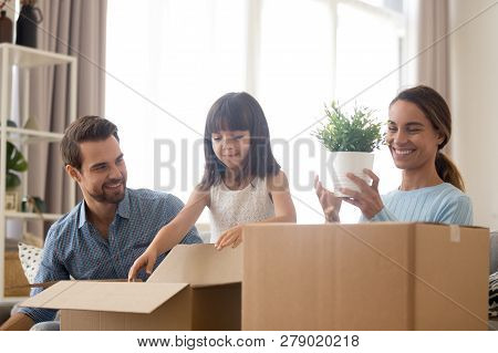 Happy Family Mom Dad And Daughter Unpacking Boxes Moving In