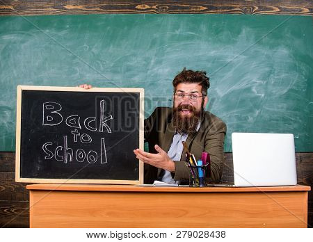 Teacher Or School Principal Welcomes With Blackboard Inscription Back To School. Beginning Of New Sc
