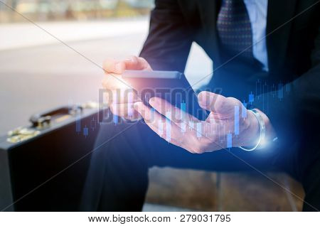 Young Investor Or Business Man Using Mobile Phone With Graphic Candle Stick Graph Chart Of Stock Mar