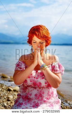 Beautiful Girl With Radiant Red Hair In Sommer Dress In A Meditative Spiritual Gesture Of Prayer.