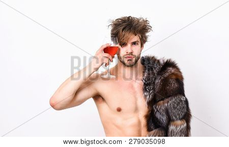 Luxury lifestyle and wellbeing. Richness and luxury concept. Guy attractive posing fur coat on naked body. Luxury status symbol. Sexy sleepy macho tousled hair drink wine or alcohol isolated on white poster