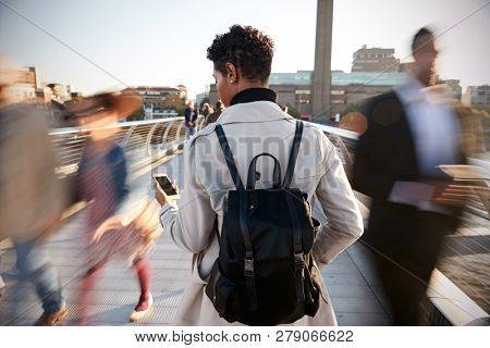 Back view of young adult woman standing on Millennium Bridge, London, using smartphone, motion blur poster