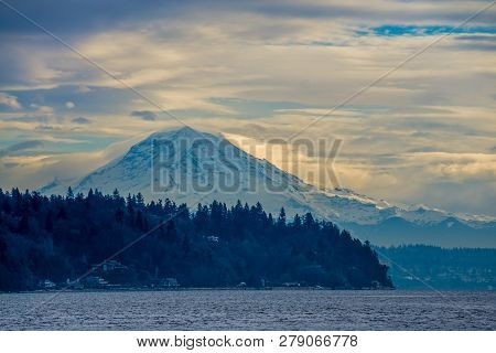 Clouds Hover Over Mount Rainier Across The Puget Sound.