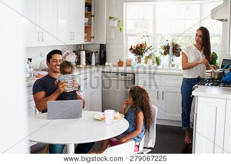 Young Hispanic family in their kitchen, dad holding baby, mum cooking at the hob