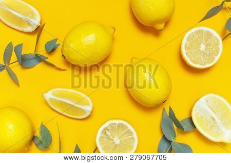 Ripe Juicy Lemons And Green Eucalyptus Twigs On Bright Yellow Background. Lemon Fruit, Citrus Minima