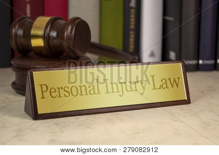 Golden Sign On A Table With Law Book And Gavel With Personal Injury Law