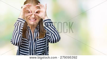Middle age mature business woman over isolated background doing ok gesture like binoculars sticking tongue out, eyes looking through fingers. Crazy expression.