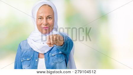 Middle age eastern arab woman wearing arabian hijab over isolated background Punching fist to fight, aggressive and angry attack, threat and violence