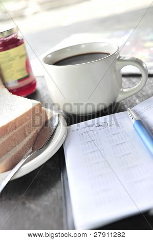 A person jotting down year 2012 diary during breakfast time in shallow depth of field