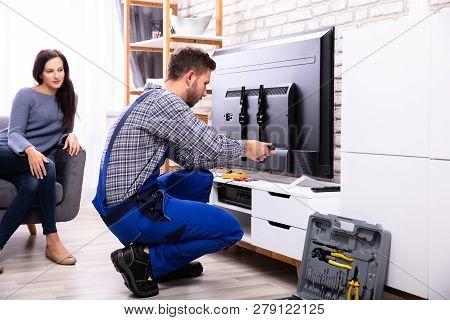 Woman Sitting On Sofa Near Male Technician Repairing Television