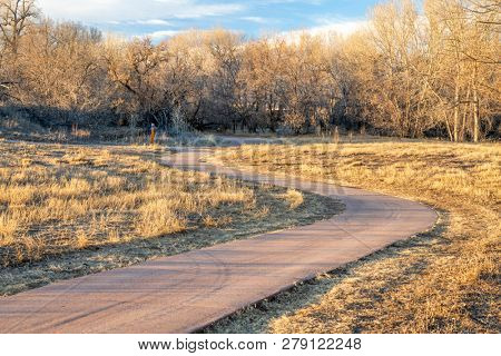 windy bike trail in late fall or winter scenery along the Poudre River in northern Colorado