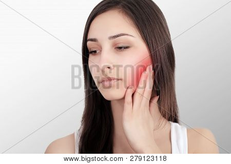 Woman In Pain. Closeup Of Beautiful Young Woman Feeling Painful Toothache, Touching Face With Hand.