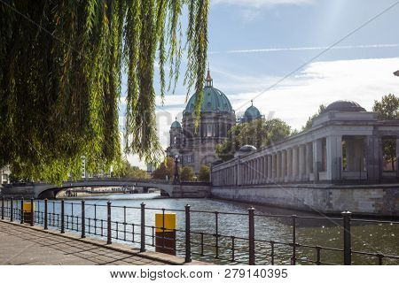 Berliner Dom, cathedral church on island museum in Berlin, Germany. View through green foliage. Blue sky background.