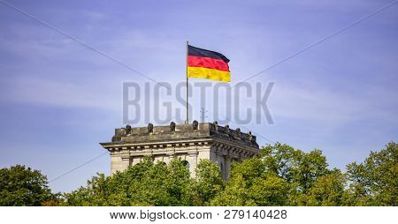 German flag waving on silver flagpole, Reichstag building in Berlin. Blue sky with clouds background, trees in front of building.
