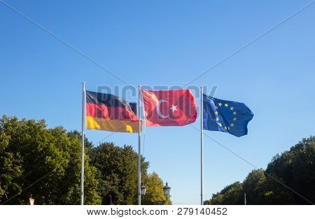 German, European Union, Turkey waving flags on white poles. Looking for co-operation about immigration. Nature and blue sky background.