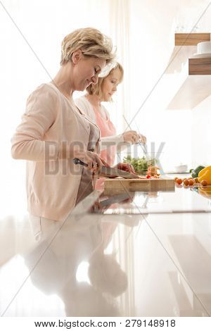Mature women preparing meal at countertop in kitchen