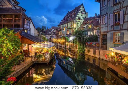 Colmar, France. Half-timbered Houses And Verandas Of Restaurants Reflecting In The Water At Dusk In