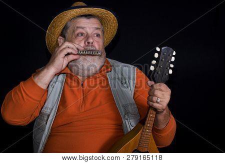 Senior Musician Playing Mouth-organ While Holding Mandolin
