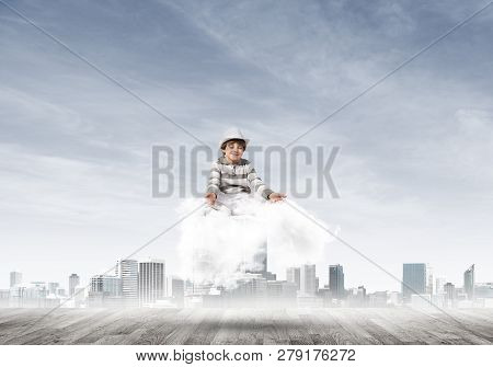 Young Little Boy Keeping Eyes Closed And Looking Concentrated While Meditating On Cloud Above Wooden