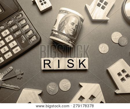 Wooden Houses, A Calculator, Keys, Coins And Blocks With The Word Risk. The Risks Of Investing In Re