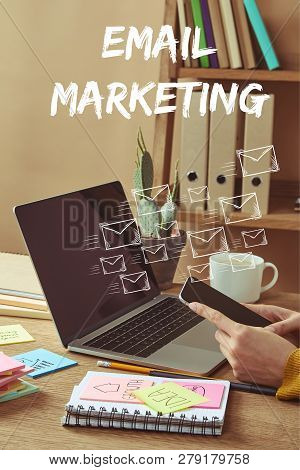 Cropped Image Of Woman Holding Smartphone With Email Icons And Email Marketing Lettering At Table Wi