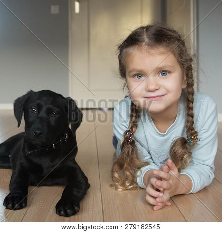 Child And Puppy Are Happy. Animal Care Concept.