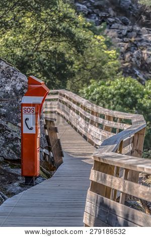 View Of Wooden Suspended Pedestrian Walkway With A Small Emergency Telephone Booth, Overlooking The