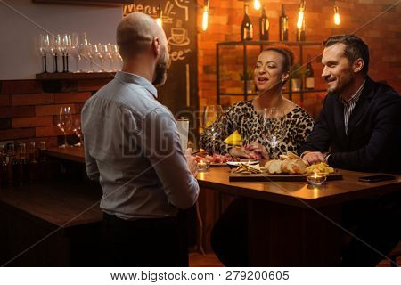 Couple talking to bartender behind bar counter in a cafe