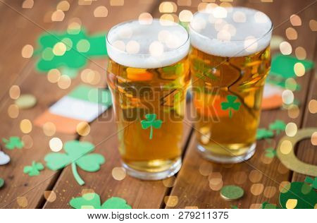 st patricks day, holidays and celebration concept - two glasses of draft light beer and party props on wooden table