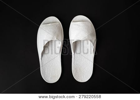 Pair Of White House Slippers On Black Background. Top View Of Disposable Slippers In Dark Contrasty