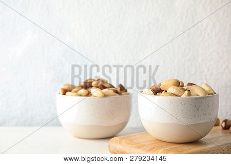 Bowls With Tasty Brazil Nuts On Table. Space For Text