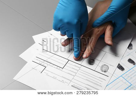 Investigator Taking Fingerprints Of Suspect On Grey Table, Closeup. Space For Text