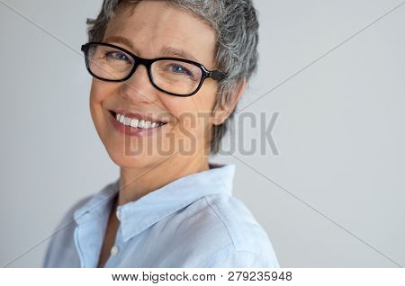 Portrait of senior woman with eyeglasses looking at camera isolated on gray background. Cheerful mature business woman wearing spectacles and smiling. Closeup face of successful entrepreneur laughing.