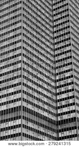 Exterior view on a skyscraper with the repetitive pattern of the facade in black and white. poster