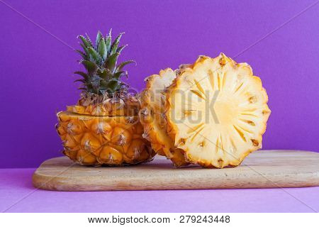 Pineapple Slices On A Cutting Board, Purple Violet Background