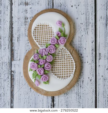 Cookie Covered With Glaze Made In A Form Of Number Eight With Sring Flowers On White Wooden Backgrou