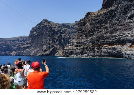 Tenerife, Canary Islands, Spain - July 26, 2018: Tourists Take Pictures Of The Vertical Cliffs Acant