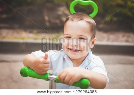 Lovely Small Smiling Infant Boy Riding A Green Trike In The Park. Concept Of Happy Childhood