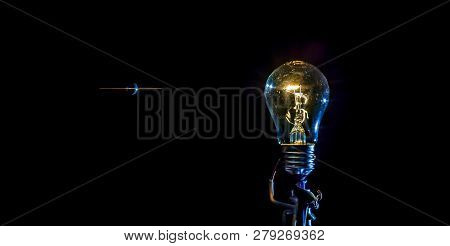 Cosmic Explosion Of A Burning Light Bulb With Flying Splinters And Smoke On A Black Background With
