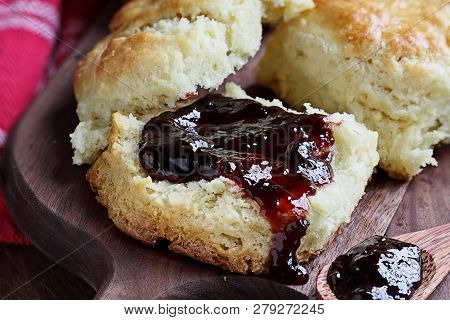 Homemade Berry Preserves Dripping Over Fresh Buttermilk Southern Biscuits Or Scones Over Rustic Cutt