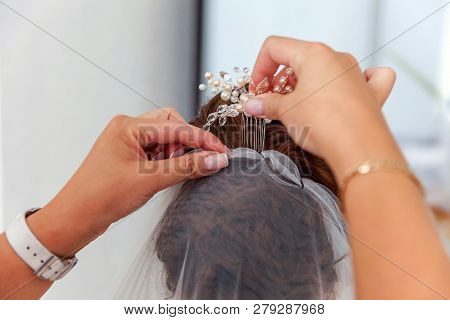 Bridesmaid Preparing Bride For Wedding Day. Bridesmaid Helping Bride Put On Her Wedding White Veil B