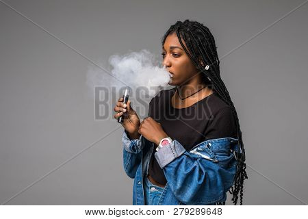 Portrait Of Guy Holding Vape Device And Exhaling Cloud Of Smoke Isolated On Blue Background.
