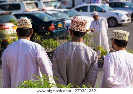 Three Omani Men Shoulders In Traditional Clothes With Dishdasha And Kuma