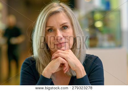 Thoughtful Determined Middle-aged Woman Scrutinising The Camera With Her Chin Resting On Her Hands