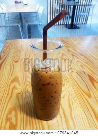 Ice Coffee In A Tall Glass Over Wooden Table. Cold Summer Drink.
