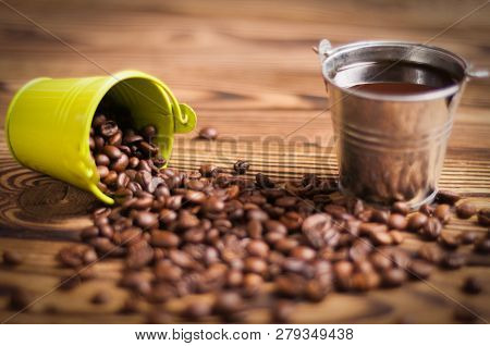 Full Zinked Bucket Of Black Coffee Near Roasted Beans Poured Out Of Green Metal Bucket With Handle O